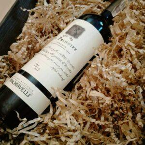 Ekologiczne wiórka wypełniające, wypełniają pudełko prezentowe zawierające butelkę wina, która leży bezpiecznie na wiórkach papierowych